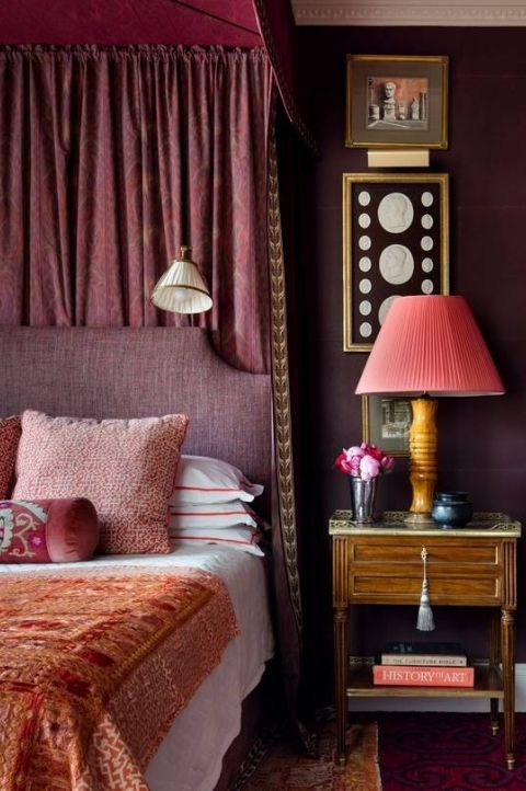 classical maximalist bedroom with roman and greek art pieces, red accessories and bedframe