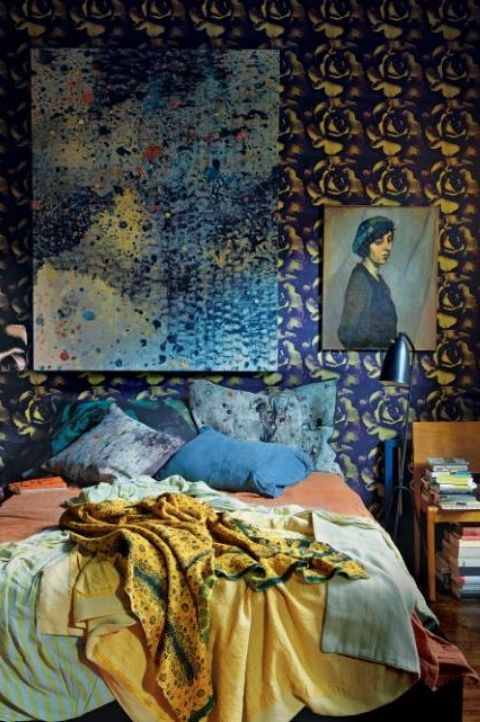 art maximalist bedroom with blue, gold and orange interior decor, large queen bed, 1970's wallpaper
