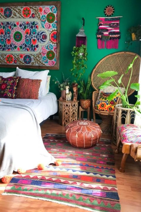 boho hippie maximalist bedroom with green walls, textured rugs, plants, white bedding