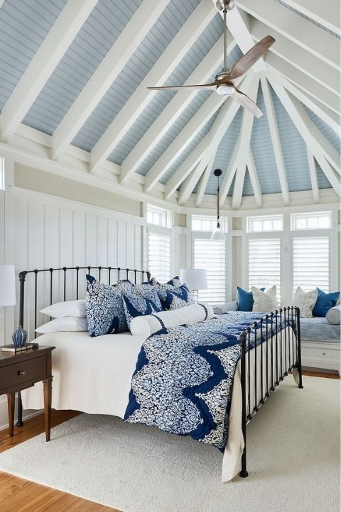 hamptons style coastal bedroom with bright blue accessories