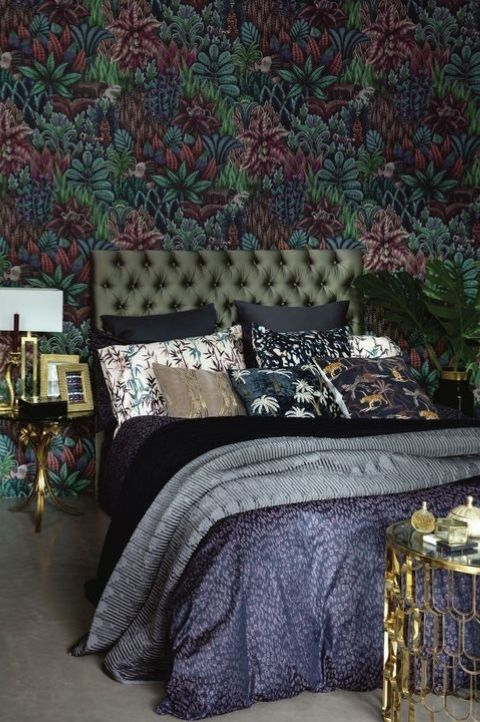 dark maximalist bedroom with patterned wallpaper and light wood flooring
