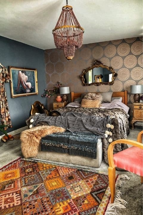 elegant maximalist bedroom, small mounted mirror, red and black furnishings, dark king bed