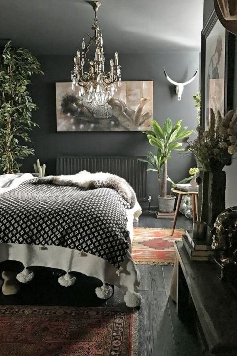 grey maximalist bedroom with textured linens, animal skull and vintage art pieces