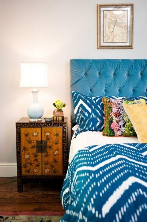 maximalist master bedroom with light blue bedframe, white furnishings, off white walls, dark oak nightstand