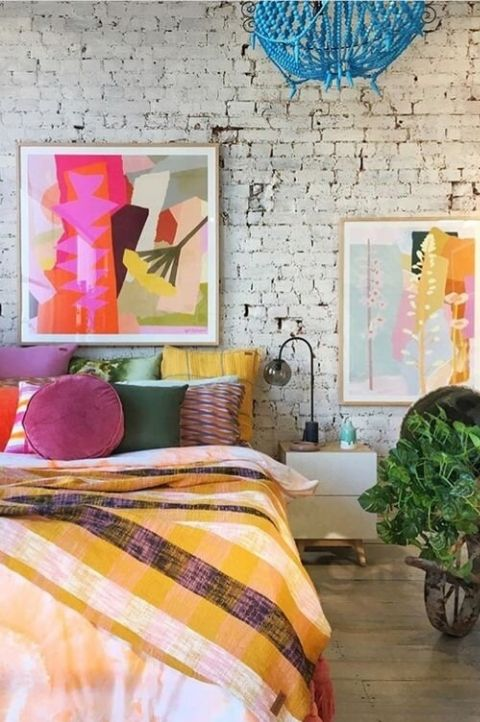 maximalist bedroom with exposed brick wall, colorful geometric paintings, colored throws