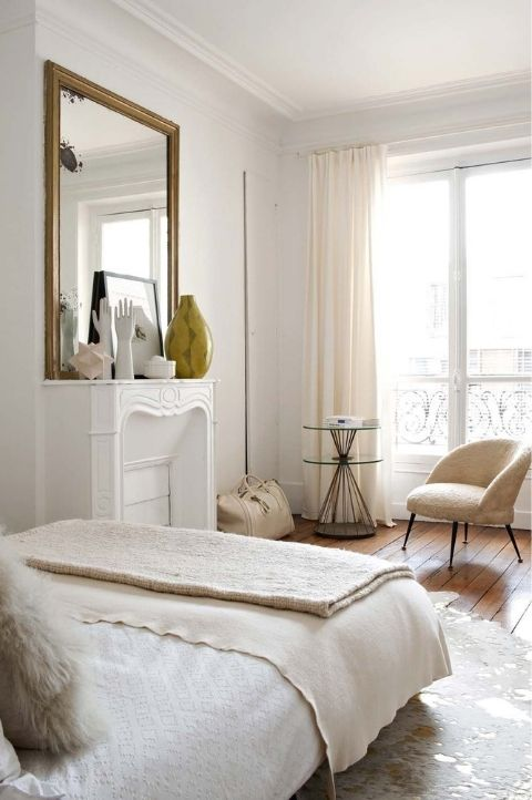 Parisian bedroom with propped up mirror and beige accessories