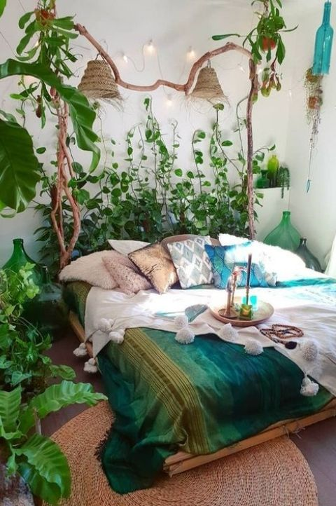 maximalist bedroom with hanging plants, blue green throws, white wash walls