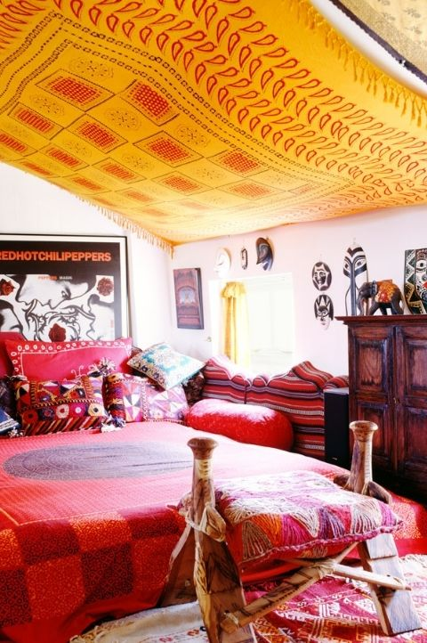 red bold maximalist bedroom with red interior decor, orange hanging canopy, dark oak drawers