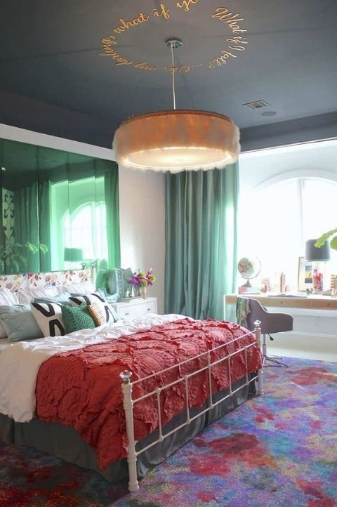 retro themed maximalist bedroom with patterned rug, green drapes, hanging light, red bed throw