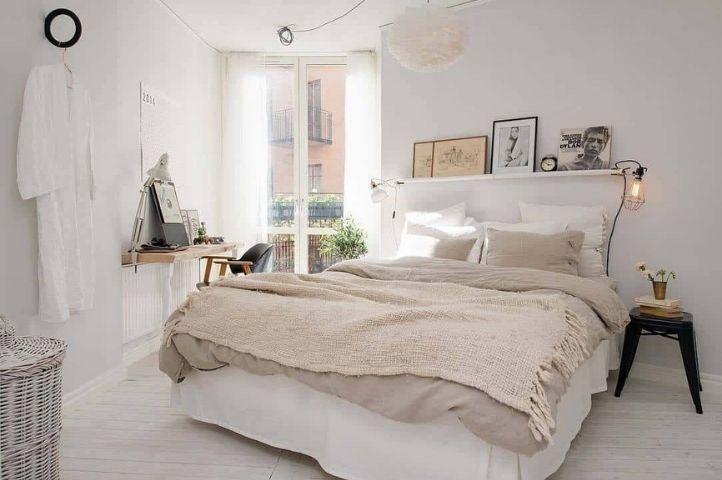 small scandinavian bedroom with beige bed throw
