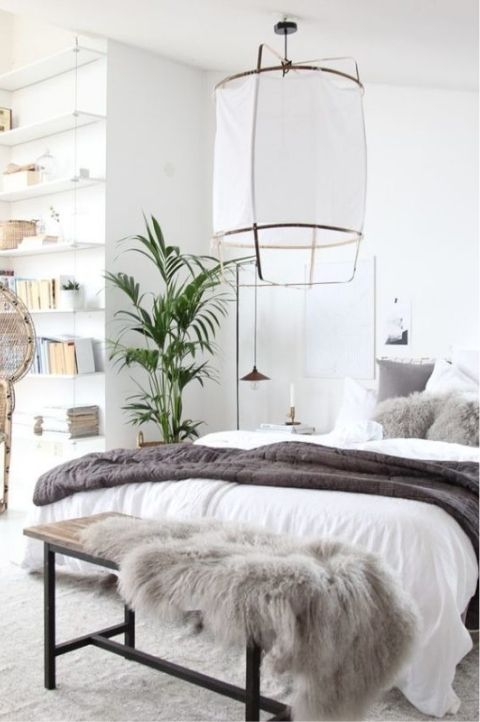 Cozy Scandinavian bedroom with grey and white furs