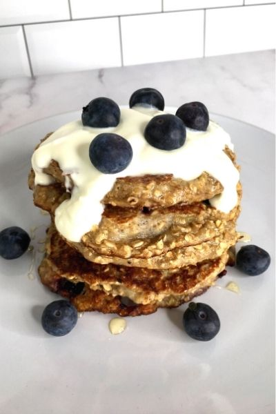a stack of healthy oat blueberry pancakes topped with greek yoghurt and fresh blueberries