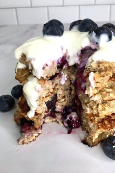 a cut stack of healthy oat blueberry pancakes with yoghurt and lots of fresh blueberries