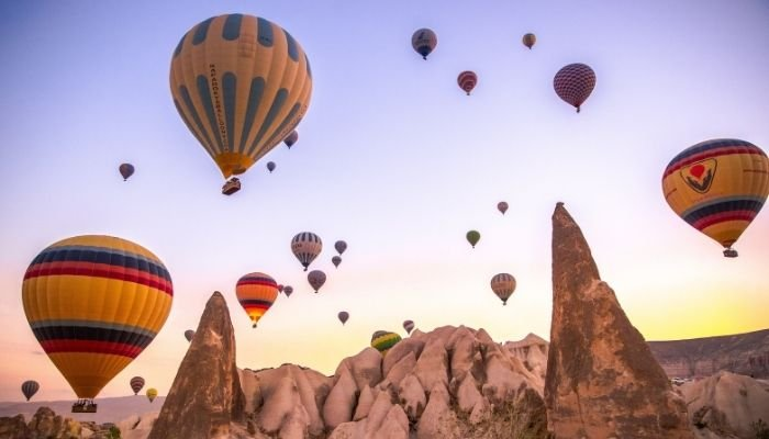multicolored hot air balloons in the sky at sunrise