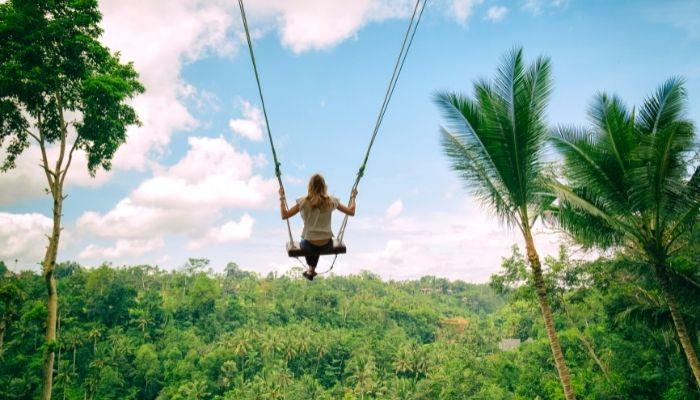 a woman on an open swing in indonesia, crazy bucket list idea