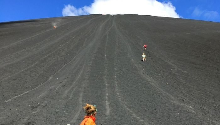 a woman looking up at the side of a volcano after surfing